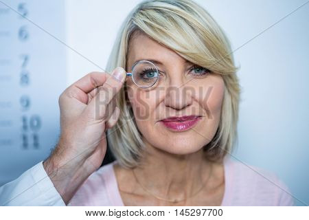 Optometrist examining female patient through ophthalmoscope in magnifying glass