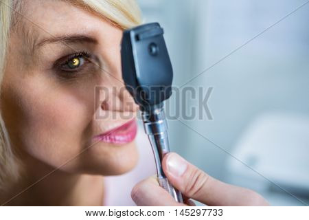 Optometrist examining female patient through ophthalmoscope in ophthalmology clinic