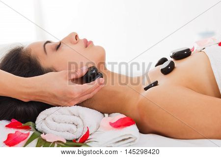 Black marble stone massage in spa. Female beautician doctor with patient in wellness center. Professional cosmetologist make relaxation procedure to beautiful indian girl in beauty parlor.