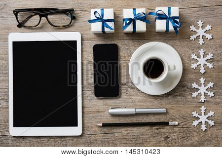Top view of desk with digital tablet, smart phone, coffee, eyeglasses, and xmas decorations. High angle view of business desk with christmas small box with blue ribbon and snowflakes with glitter.