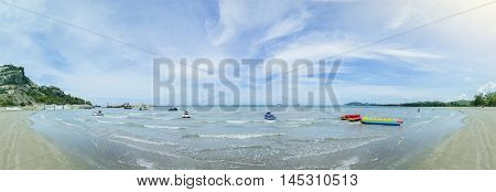 panorama view of the blue sea and clean beach with beautiful blue sky and cloud jetski banana boat on a surface of sea filtered image