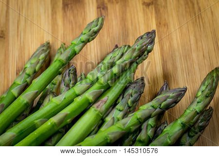 Fresh asparagus reading for preparation on a bamboo cutting board.