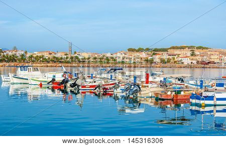 The colorful motor boats along the shipyard with the old town and medieval Fortezza citadel on the background Rethymno Crete Greece.