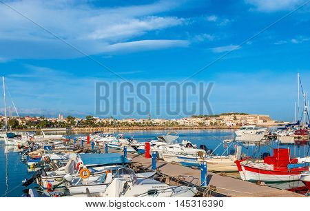 RETHYMNO GREECE - OCTOBER 16 2013: The motor boats and yachts in the new port with the medieval Fortezza citadel on the background on October 16 in Rethymno.