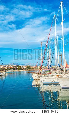 The bright blue waters of the Aegan Sea reflect the white yachts moored in the new port Rethymno Crete Greece.