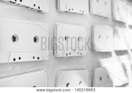 Audio cassettes are covered with white acrylic paint. Pictures taken at an angle. Excellent retro. Creative decor. Black and white photo. Secured by modern style. Vintage tapes.