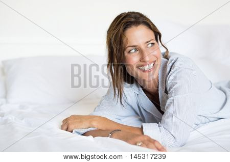 Cheerful woman lying on bed. Portrait of beautiful young woman thinking on bed in the morning. Happy smiling woman daydreaming on her future.