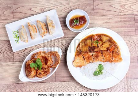 Rice with deep fried dolly fish in japanese yellow curry served with side dish of stuffing flour  and onion ring on wood.