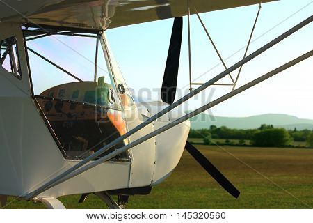 Ultralight aircraft in sunset on airport grass with reflection