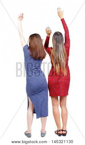 Back view of two dancing young women. . backside view of person. Rear view people collection. Isolated over white background. Two girls in dresses dancing hands up.