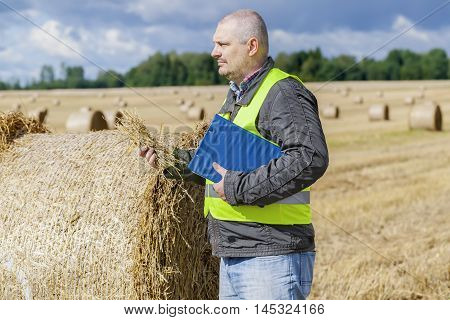 Farmer with straw in hand near straw bales on field