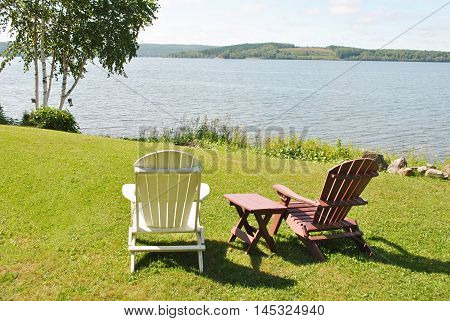 Two Adirondack Chairs with a Table Facing the Lake View