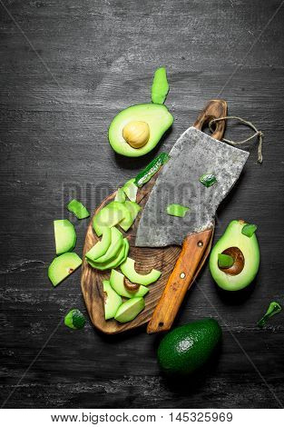 Sliced avocado with a hatchet on the Board. On a black wooden background. Top view.