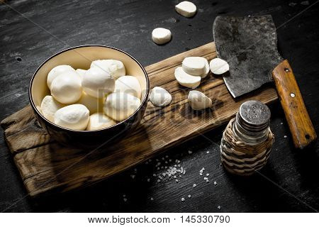 Fresh mozzarella with a hatchet for cutting. On a black wooden background.