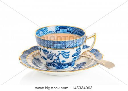 Cup of breakfast tea in antique teacup and saucer with spoon on a white background