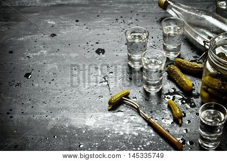 Russian style. Bottle vodka with shot glasses and pickled cucumbers . On a black wooden background.