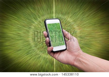 Hand holding smartphone with green field on screen on green background