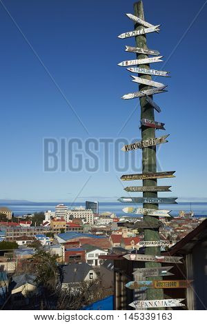 PUNTA ARENAS, CHILE - AUGUST 25, 2016: Signpost to locations around the world in Punta Arenas in southern Chile overlooking the Strait of Magellan.