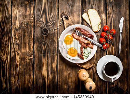 Fresh Breakfast with Cup of coffee, fried Beck with eggs and tomatoes. On a wooden table.