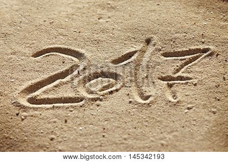 New year 2017 written on sand .