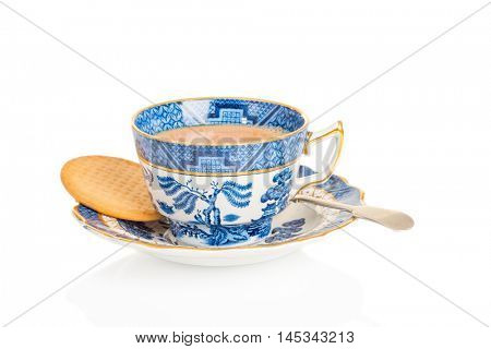 Cup of tea in an antique teacup and saucer with biscuit on a white background