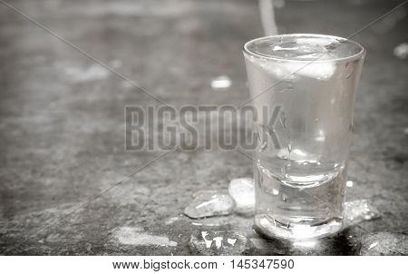 The glass of cold vodka. On the stone table.