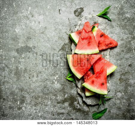 Chunks of watermelon with mint branches. On the stone table.