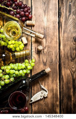 White and red wine with branches of grapes , a corkscrew and corks. On a wooden table.