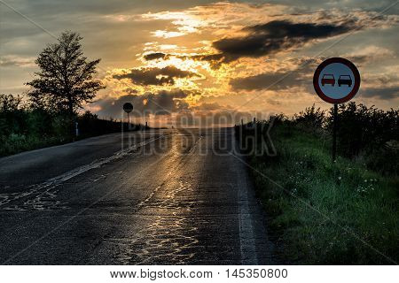 No overtaking sign by an old and damaged road in a dramatic sunset