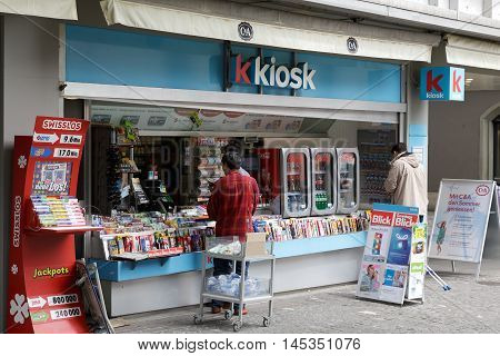 LUCERNE SWITZERLAND - MAY 11 2016: Unrecognized passers do some shopping at a kiosk. Retail sales in heavily used areas provides daily access to many needed products and small gifts