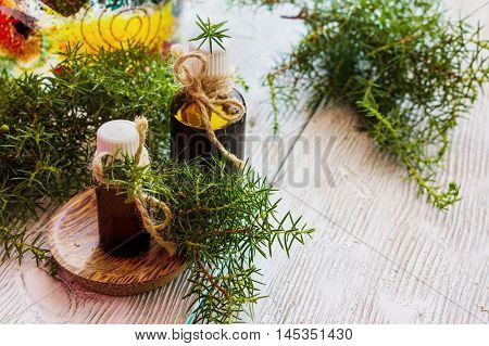 Juniper essential oil in a glass bottle on a wooden table. Used in medicine cosmetics and aromatherapy. Fresh green sprigs. Selective focus.