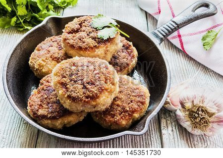 Homemade cutlets roasted or baked in black cast-iron skillet. Wooden table fresh vegetables and parsley