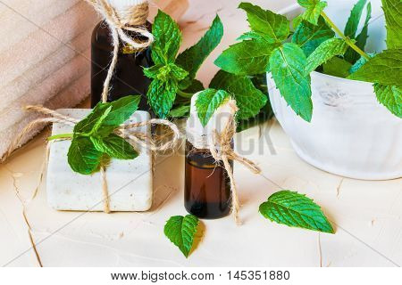 Peppermint essential oil in a glass bottle on a light table. Used in medicine cosmetics and aromatherapy. White towels fresh leaves and a piece of soap. Selective focus.