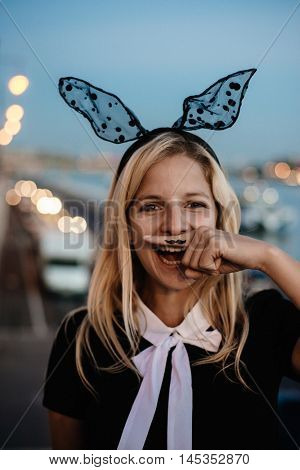 blonde woman having dun outdoor with bunny hair and fake mustache