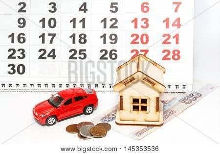 Wooden house red car and the Russian money on a calendar background