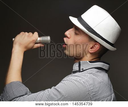 life style and people concept: young singer man with microphone