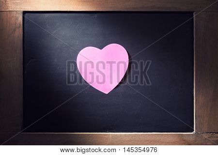 Empty pink hearted shape post-it note on blackboard with concentrated light beam for dramatic feel vintage retro look