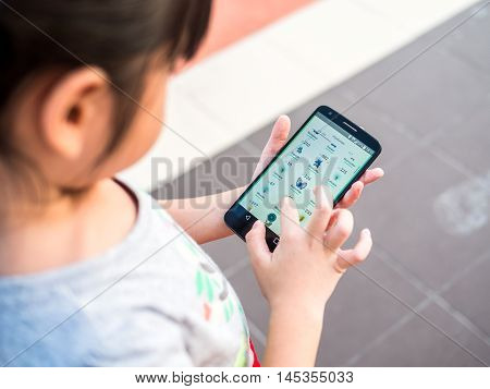 Chonburi, Thailand- September 2, 2016: Asian Little Girl Playing A Pokemon Go Game Outdoors. Pokemon
