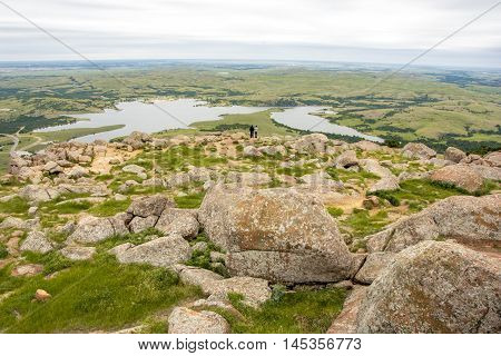 A wide angle shot of a couple enjoying a sweeping overlook at Wichita Mountains National Wildlife Refuge in Oklahoma.