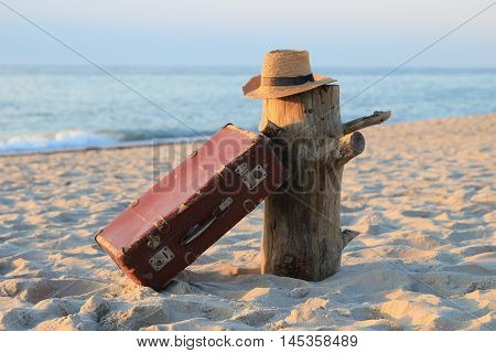 suitcase old and a hat on a stub on the seashore
