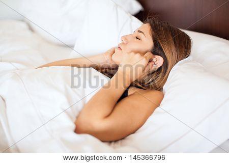 Woman Wearing Earplugs In Bed