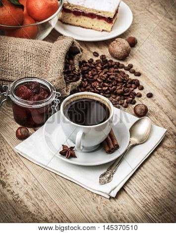Fragrant strong coffee with sweet dessert and bean on old wooden board in rustic style