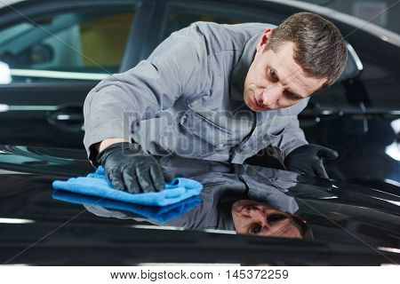 Repair man worker polishing automobile car body in garage