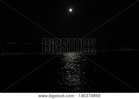 reflections of full moon on Garda lake in Italy