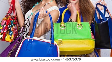 Women colored leather bags in the hands of two fashionable girls on a white background