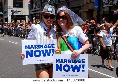 New York City - June 27 2009: Two women with marriage now signs at 40th anniversary gay pride parade on  Fifth Avenue