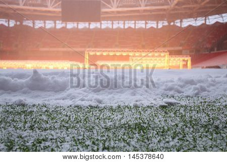 Closeup view of snow on green field in football stadium with lamps