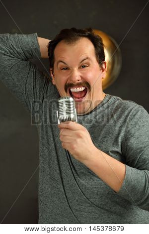Outrageous man with mustache sing into microphone in studio with lamp on wall