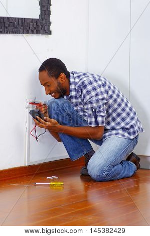 Man wearing white and blue shirt working on electrical wall socket wires using multimeter, electrician concept.