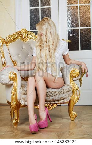Young blonde woman sits in the vintage gilt armchair.
